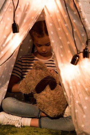 Photo pour Preteen enfant jouer avec la barbe en peluche dans wigwam avec des ampoules - image libre de droit