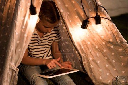 Photo pour Enfant en t-shirt rayé assis en wigwam et utilisant une tablette numérique avec écran blanc - image libre de droit