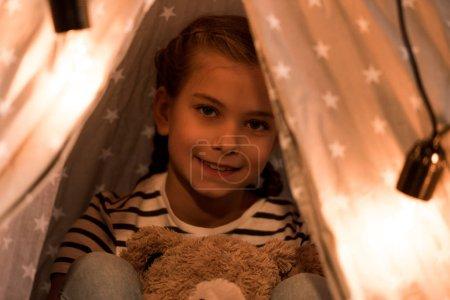 Photo pour Souriant mignon enfant avec ours en peluche regardant la caméra - image libre de droit