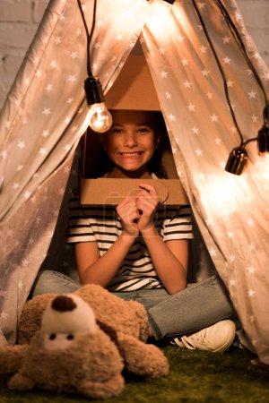 Photo pour Enfant excité dans un casque en carton assis à Wigwam avec le sourire - image libre de droit