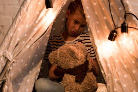 Photo pour Enfant déçu regardant l'ours en peluche assis dans wigwam à la maison - image libre de droit