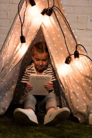 Photo pour Enfant souriant assis dans le wigwam confortable et tenant tablette numérique - image libre de droit