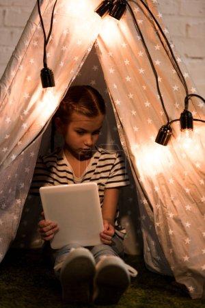 Photo pour Enfant sérieux assis dans wigwam et tenant tablette numérique dans la chambre noire - image libre de droit