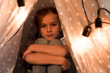 Photo pour Mignon sérieux enfant embrasser genoux et regarder caméra - image libre de droit