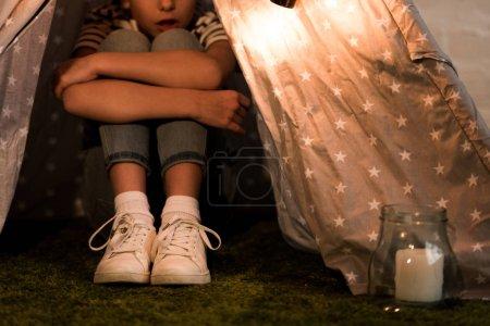 Photo pour Vue recadrée d'un enfant assis dans un wigwam et embrassant les genoux - image libre de droit