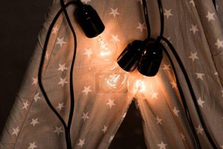Photo pour Wigwam avec des ampoules lumineuses sur fond sombre - image libre de droit