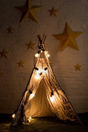 Photo pour Confortable wigwam avec des ampoules lumineuses debout dans la pièce sombre - image libre de droit