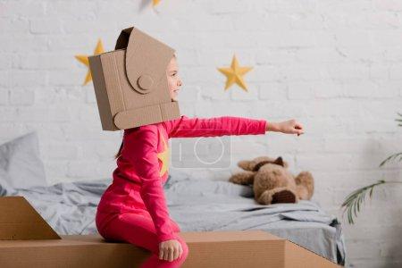 Photo pour Vue latérale de l'enfant en carton casque tenant la main vers le haut - image libre de droit