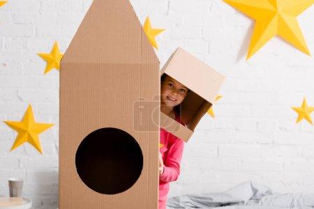 Foto de Divertido niño en pie casco de cartón cerca de cohete en dormitorio - Imagen libre de derechos