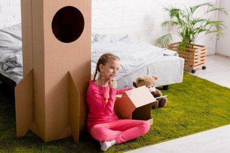 Photo pour Enfant curieux en vêtements roses assis sur le tapis près de fusée en carton - image libre de droit