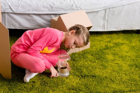 Photo for Kid sitting on green carpet and looking at plant in glass jar - Royalty Free Image