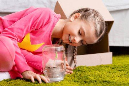 Photo pour Enfant souriant, plante en pot de verre en regardant avec intérêt - image libre de droit