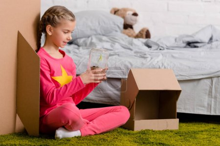 Interested kid sitting on carpet and holding plant in glass jar