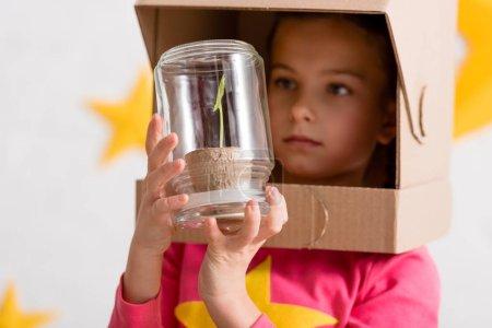 Photo pour Curieux enfant en carton casque regardant la plante en pot - image libre de droit