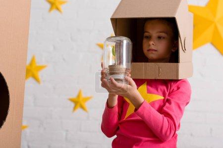 Photo pour Curieux enfant en carton casque tenant pot avec plante - image libre de droit