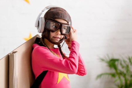 Photo pour Enfant dans le casque de vol et lunettes écoutant de la musique dans les écouteurs - image libre de droit