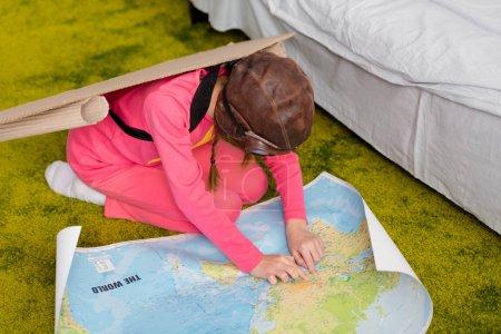 Kind in pinkfarbener Kleidung sitzt auf Teppich und schaut auf Landkarte