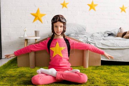 Photo pour Enfant inspiré dans le casque de vol assis dans la pose de lotus sur le tapis - image libre de droit