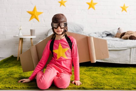 Photo pour Enfant curieux en lunettes et casque de vol assis sur le tapis vert - image libre de droit