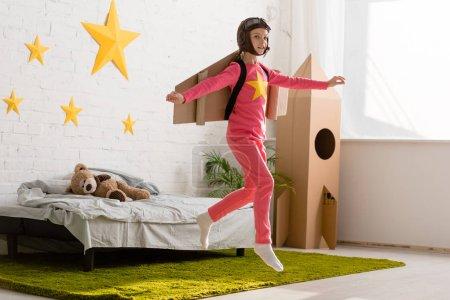 Photo pour Enfant inspiré avec des ailes en carton sautant dans la chambre avec le sourire - image libre de droit