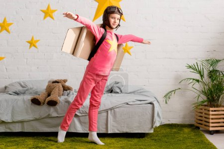 Photo for Happy kid with cardboard wings having fun in bedroom - Royalty Free Image
