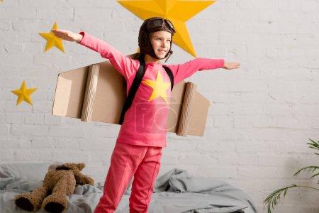 Photo pour Enfant inspiré avec des ailes en carton gesticulant dans la chambre - image libre de droit