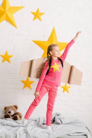 Photo pour Enfant confiant avec des ailes en carton debout sur le lit avec la main en l'air - image libre de droit