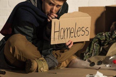 Photo pour Homme déprimé assis sur carton et maintenant carte avec texte manuscrit «sans-abri» - image libre de droit