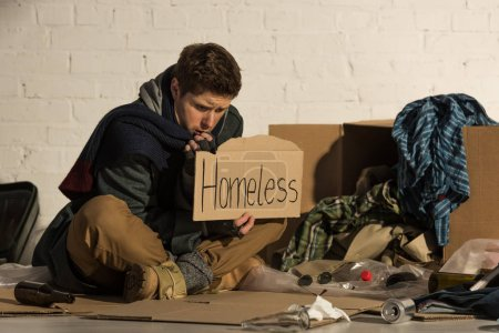 "Photo for Misery man sitting on garbage dump and holding piece of cardboard with ""homeless"" inscription - Royalty Free Image"