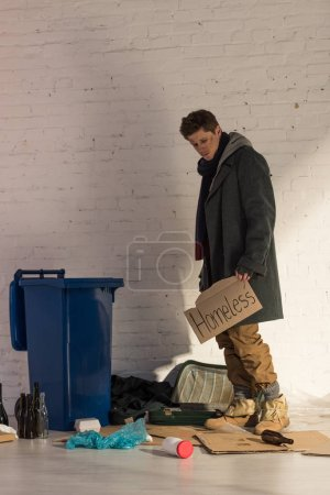 """Photo for Homeless misery man standing near trash container and holding cardboard card with """"homeless"""" handwritten text - Royalty Free Image"""