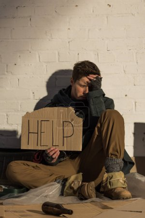 """Photo for Despaired homeless man sitting by brick wall and holding piece of cardboard with """"help"""" inscription - Royalty Free Image"""