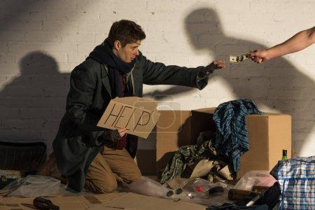 Photo pour Recadrée de l'homme par un étranger, donner de l'argent à l'homme sans-abri mendiant - image libre de droit