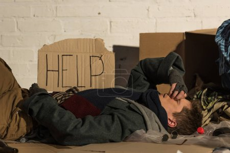 "Photo for Homeless misery man lying on cardboard, with ""help"" inscription on card - Royalty Free Image"