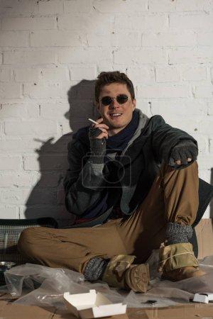 Foto de Sonriendo a sin hogar hombre fumando sentado por pared de ladrillo - Imagen libre de derechos
