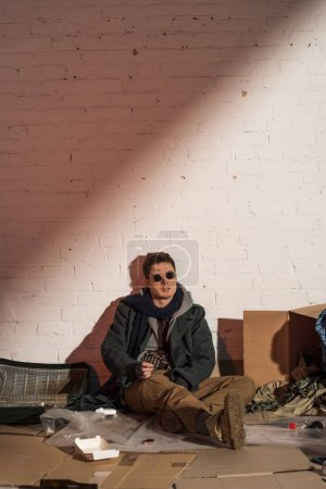 Photo for Homeless man surrounded by rubbish sitting by white brick wall - Royalty Free Image