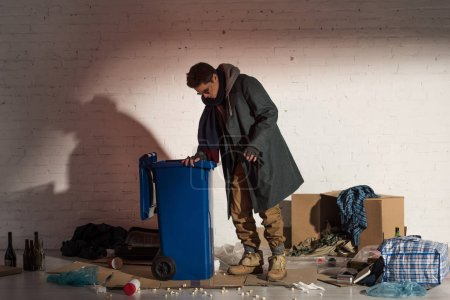 Photo for Homeless man in dark clothes rummaging in trash container - Royalty Free Image