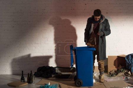 Photo for Homeless man standing near garbage container surrounded by rubbish - Royalty Free Image