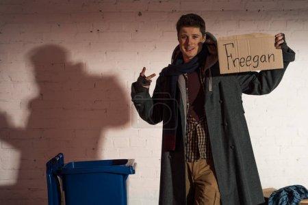 """hombre sin hogar sosteniendo tarjeta de cartón con letras """"freegan"""" y mostrando signo de victoria"""