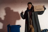 homeless man holding cardboard card with