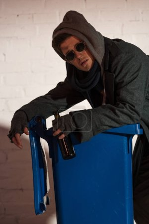 Photo for Homeless man with alcohol bottle leaning on trash container - Royalty Free Image
