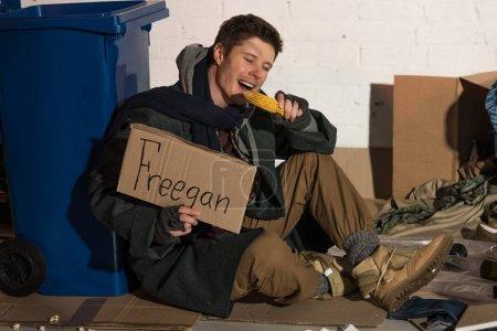 "homeless man eating corn cob and holding cardboard card with ""freegan"" inscription"