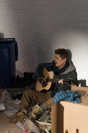 Photo for Homeless man sitting on cardboard surrounded by rubbish and playing guitar - Royalty Free Image