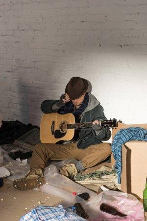 Foto de Hombre sin hogar en sombrero y guantes sin dedos guantes holding guitarra sentado rodeado de basura - Imagen libre de derechos