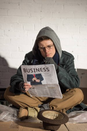 Photo for Homeless man in glasses attentively reading business newspaper - Royalty Free Image