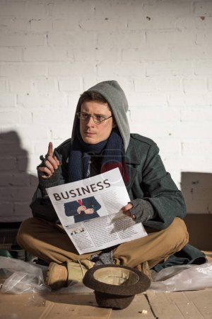 Photo for Homeless man reading business newspaper and showing idea sign - Royalty Free Image