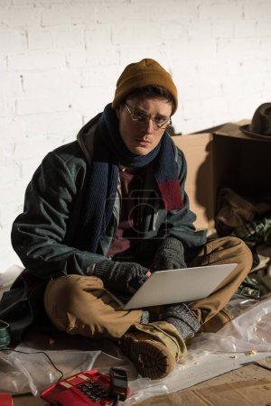 hombre sin hogar serio en gafas usando el ordenador portátil