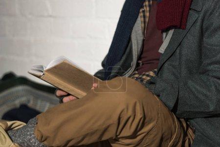 Foto de Vista recortada de hombre sin hogar lectura sentado por pared de ladrillo blanco - Imagen libre de derechos