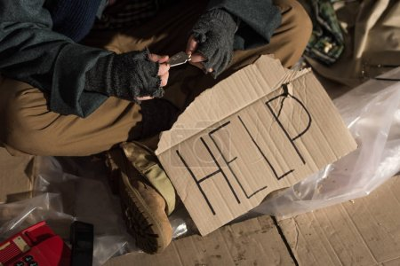 "Photo for Cropped view of homeless man sitting with cardboard card with ""help"" handwritten text - Royalty Free Image"