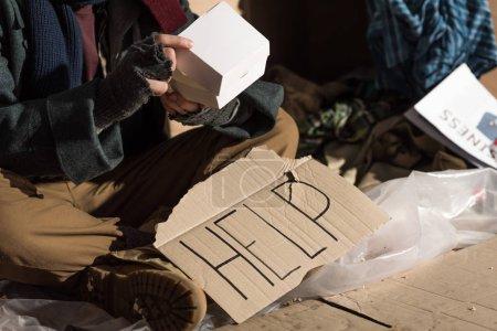 Photo pour Partielle découvre oh sans-abri homme en mitaines assis près de la carte en carton avec l'inscription «help» et la tenue de boîte de papier - image libre de droit