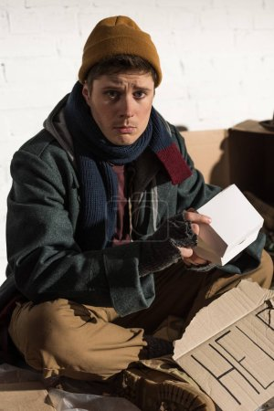"""Photo for Sad homeless man sitting with cardboard card with """"help"""" lettering and holding white paper box - Royalty Free Image"""